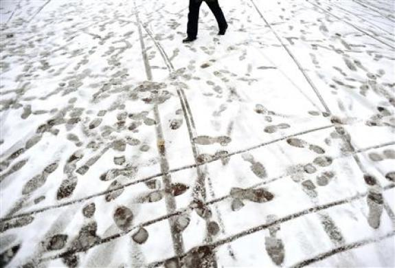 A man strolls down a snow covered street in central London December 2, 2010. REUTERS/Dylan Martinez